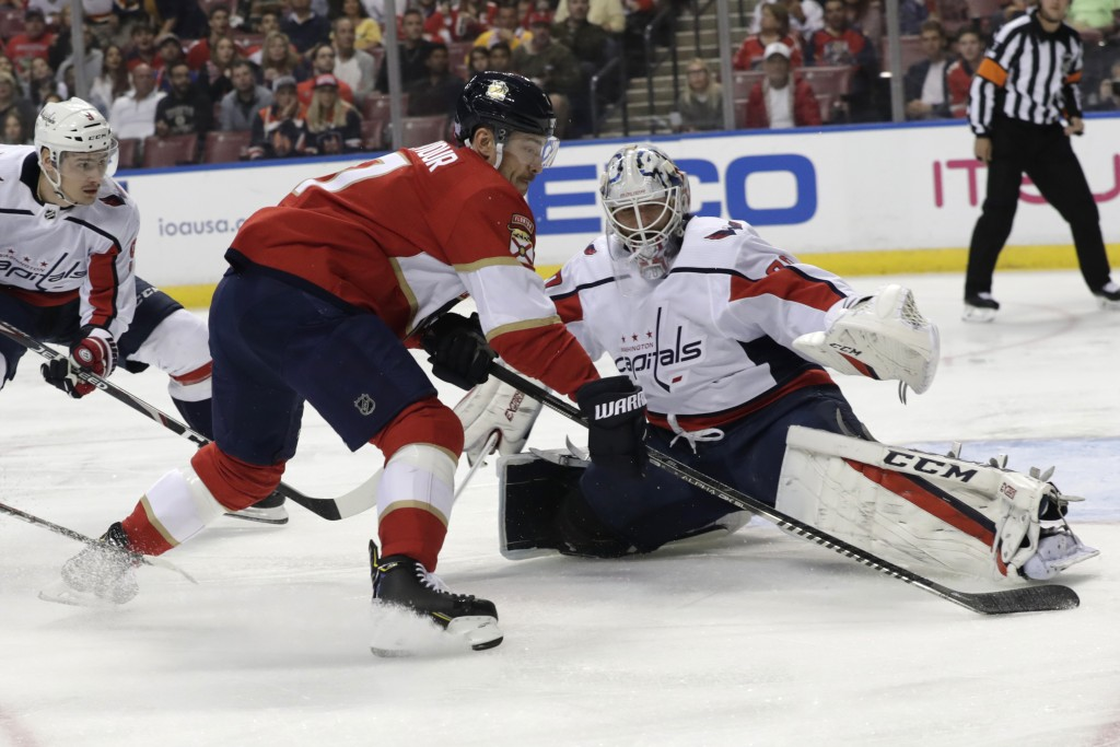 Washington Capitals goaltender Braden Holtby, front right, stops a shot by Florida Panthers center Colton Sceviour, front left, during the first perio...