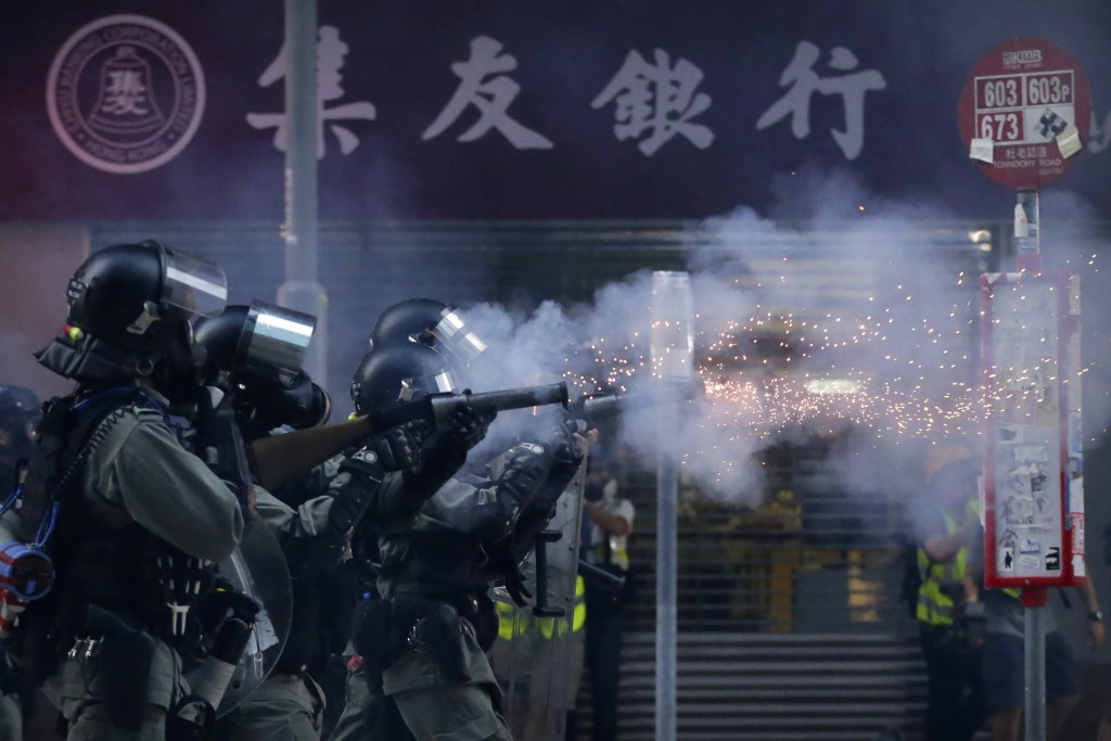 In this Saturday, Nov. 2, 2019, file photo, police in riot gear fire tear gas during a protest in Hong Kong. Hong Kong riot police fired multiple roun...