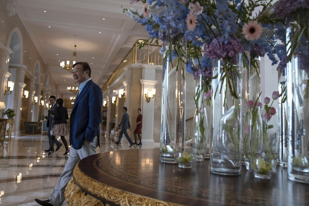 In this Aug. 20, 2019, photo, Huawei's founder Ren Zhengfei, walks past an opulent corridor in the company campus in Shenzhen in Southern China's Guan...