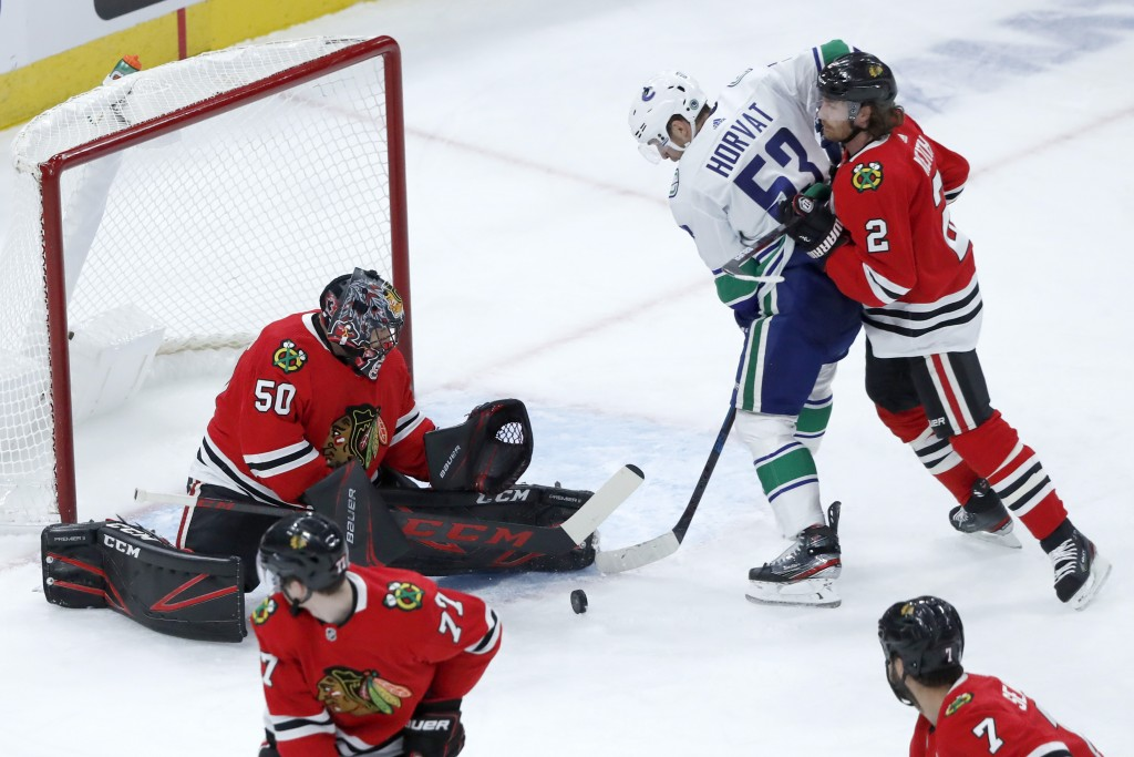 Chicago Blackhawks goaltender Corey Crawford (50) makes a save as defenseman Duncan Keith (2) keeps Vancouver Canucks center Bo Horvat from getting a ...
