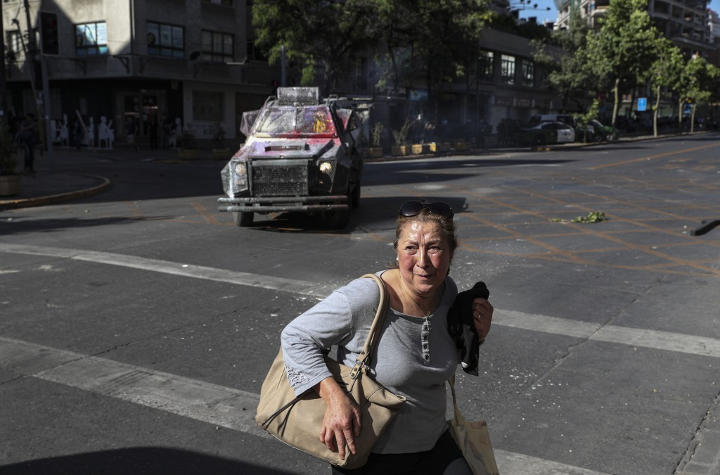 A woman crosses a street in front of an armored vehicle that is in pursuit of anti-government protesters, in Santiago, Chile, Thursday, Nov. 7, 2019. ...