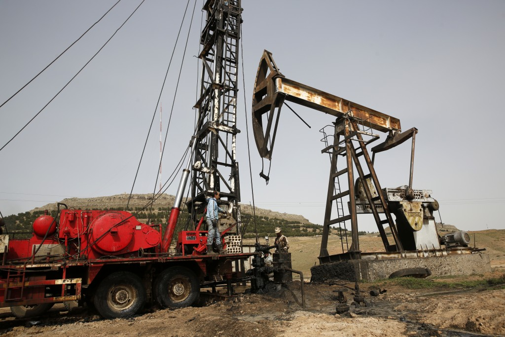 FILE - This March 27, 2018 file photo shows Syrian workers fixing pipes of an oil well at an oil field controlled by a U.S-backed Kurdish group, in Rm...