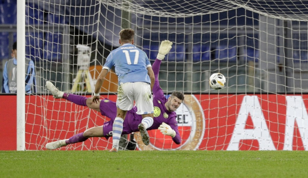 Celtic's goalkeeper Fraser Forster, background, makes a save in front of Lazio's Ciro Immobile during an Europa League group E soccer match between La...