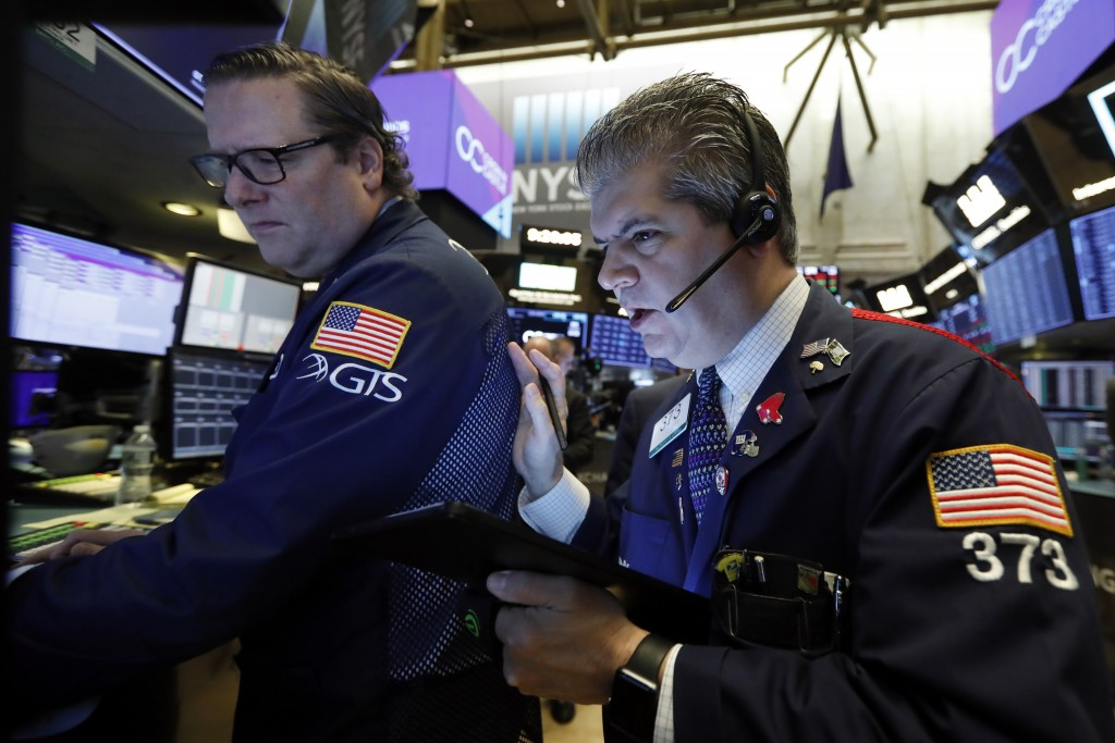 FILE - In this Oct. 29, 2019, file photo specialist Gregg Maloney, left, and trader John Panin work on the floor of the New York Stock Exchange. The U...