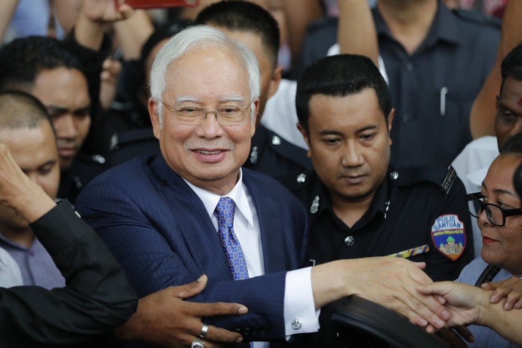 FILE - In this April 3, 2019, file photo, former Prime Minister Najib Razak, center, gets into a car after his court appearance at the Kuala Lumpur Hi...