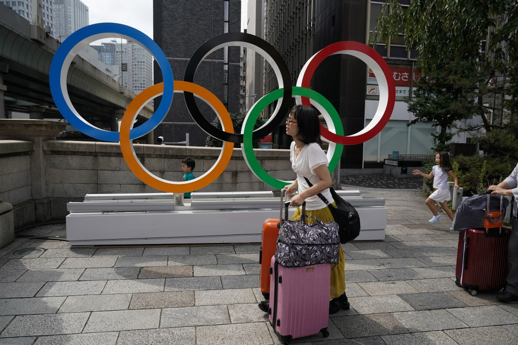 FILE - In this Aug. 19, 2019, file photo, tourists walk with their luggage past the Olympic rings in Tokyo. Frustrated residents of Japan got another ...