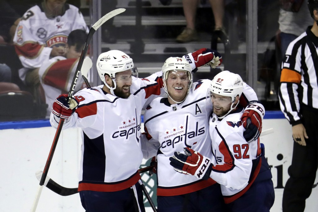 Washington Capitals right wing Tom Wilson, left, celebrates with defenseman John Carlson, center, and center Evgeny Kuznetsov (92) after scoring a goa...