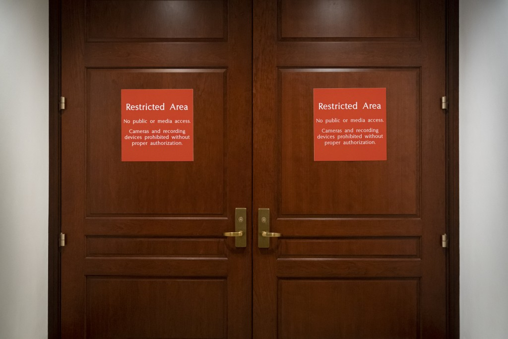 In this Nov. 6, 2019, photo, bright red signs alert non-authorized personnel at the entrance to the House SCIF, the Sensitive Compartmented Informatio...