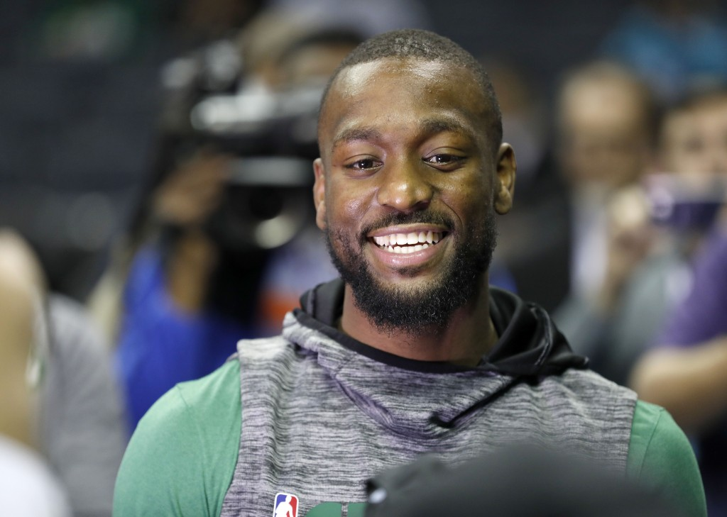 Boston Celtics' Kemba Walker smiles with friends as he makes his way onto the Charlotte Hornets' court before an NBA basketball game between the Celti...