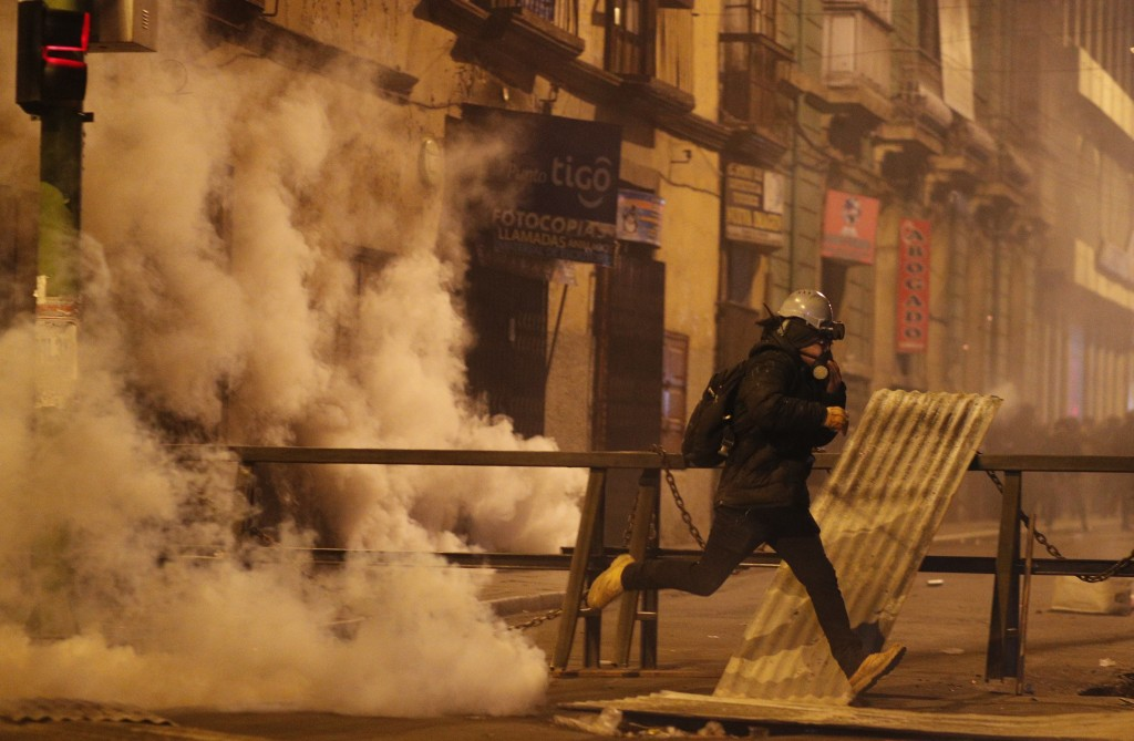 A demonstrator runs for cover as police launch tear gas during a protest against President Evo Morales' reelection, in La Paz, Bolivia, Thursday, Nov....