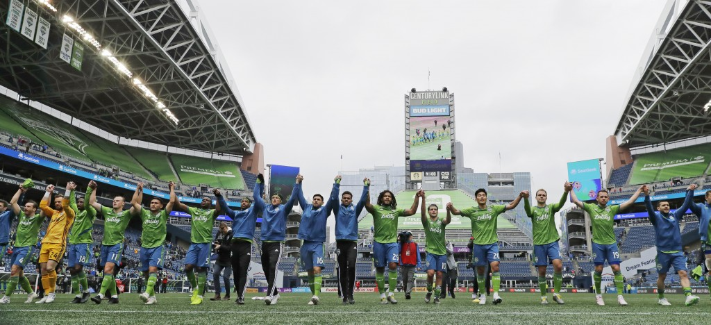 FILE - In this April 13, 2019, file photo, Seattle Sounders players celebrate after they beat Toronto FC 3-2 in an MLS soccer match at CenturyLink Fie...