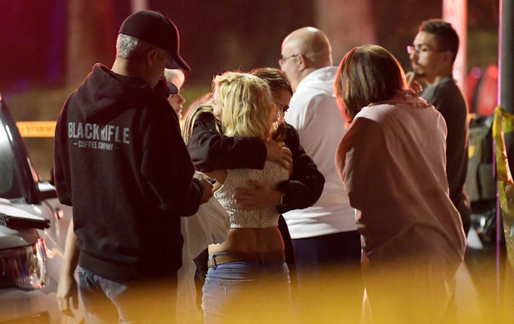 FILE - In this Thursday, Nov. 8, 2018, file photo, people comfort each other as they stand near the scene in Thousand Oaks, Calif., where a gunman ope...
