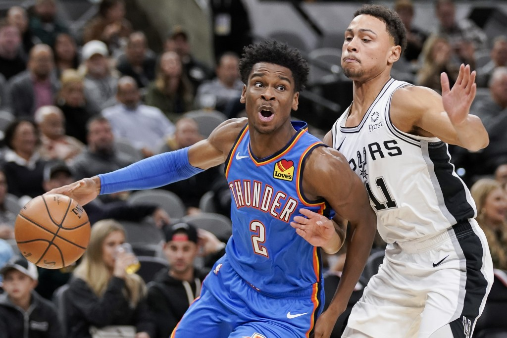 Oklahoma City Thunder's Shai Gilgeous-Alexander (2) drives against San Antonio Spurs' Bryn Forbes during the first half of an NBA basketball game, Thu...