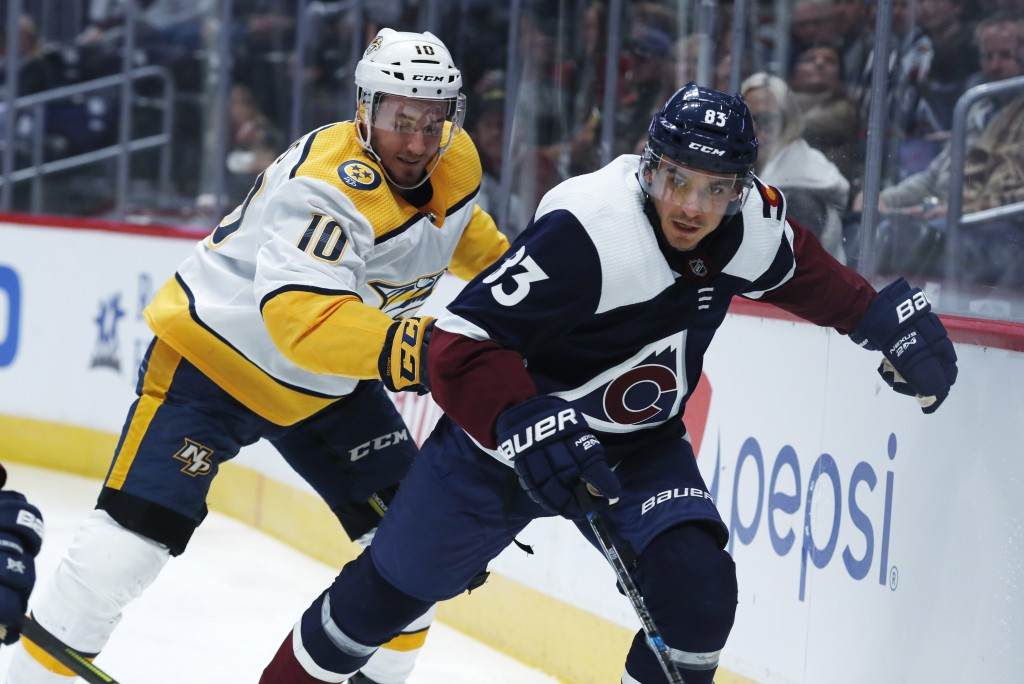 Nashville Predators center Colton Sissons, back, and Colorado Avalanche left wing Matt Nieto pursue the puck along the boards during the first period ...
