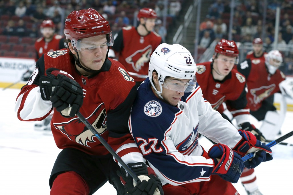 Arizona Coyotes center Barrett Hayton (29) and Columbus Blue Jackets left wing Sonny Milano (22) fight for the puck in the first period during an NHL ...