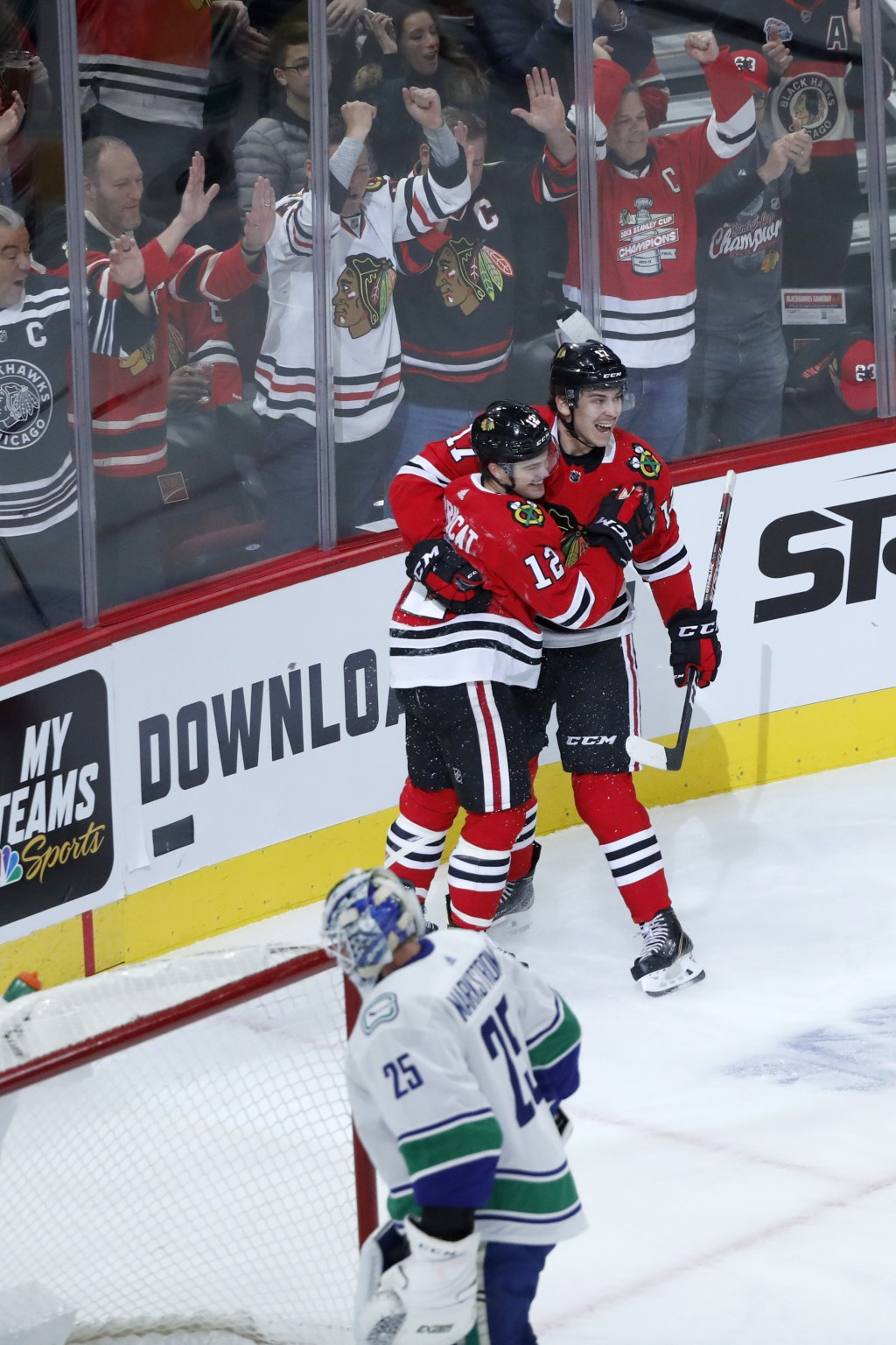 Chicago Blackhawks' Alex DeBrincat (12) and Dylan Strome celebrate DeBrincat's goal during the first period of an NHL hockey game against the Vancouve...