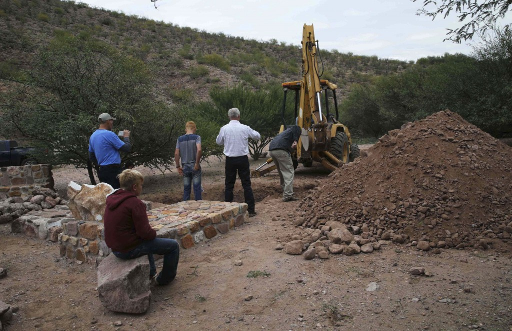 Men stand around a grave being dug for several of the women and children related to the extended LeBaron family who were killed by drug cartel gunmen,...