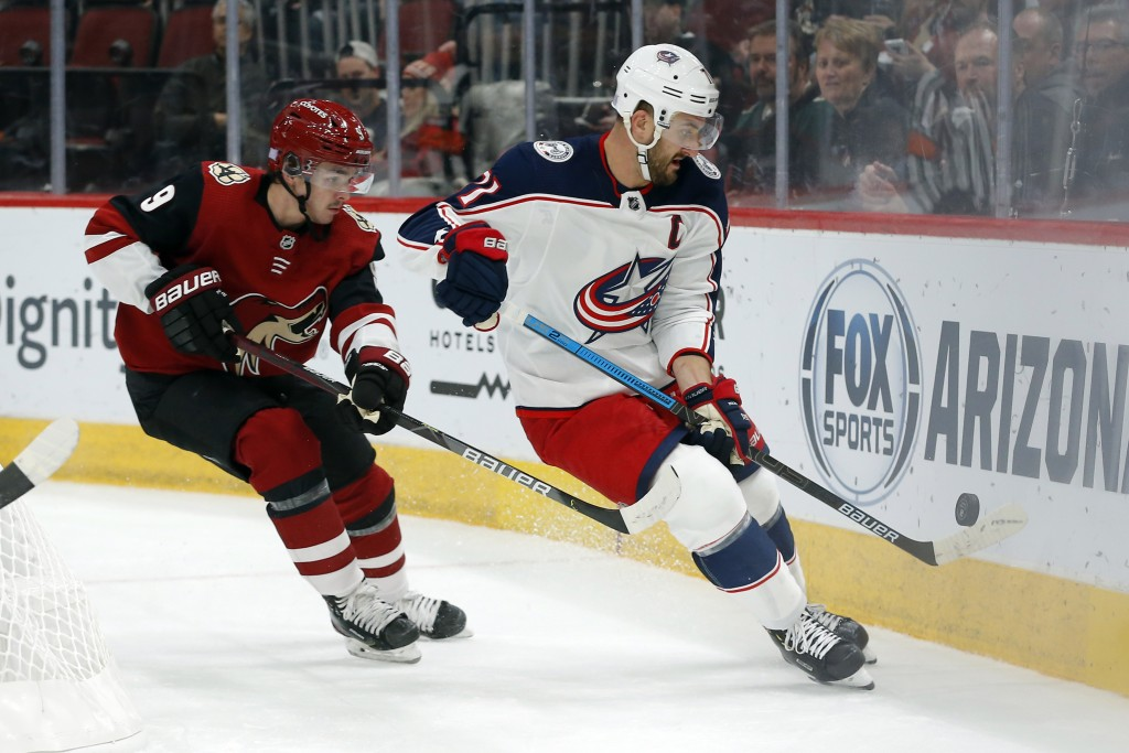 Columbus Blue Jackets left wing Nick Foligno, right, shields Arizona Coyotes center Clayton Keller (9) from the puck in the first period during an NHL...
