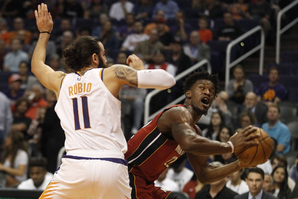 Miami Heat's Jimmy Butler (22) looks to the basket against Phoenix Suns' Ricky Rubio (11) during the first half of an NBA basketball game Thursday, No...