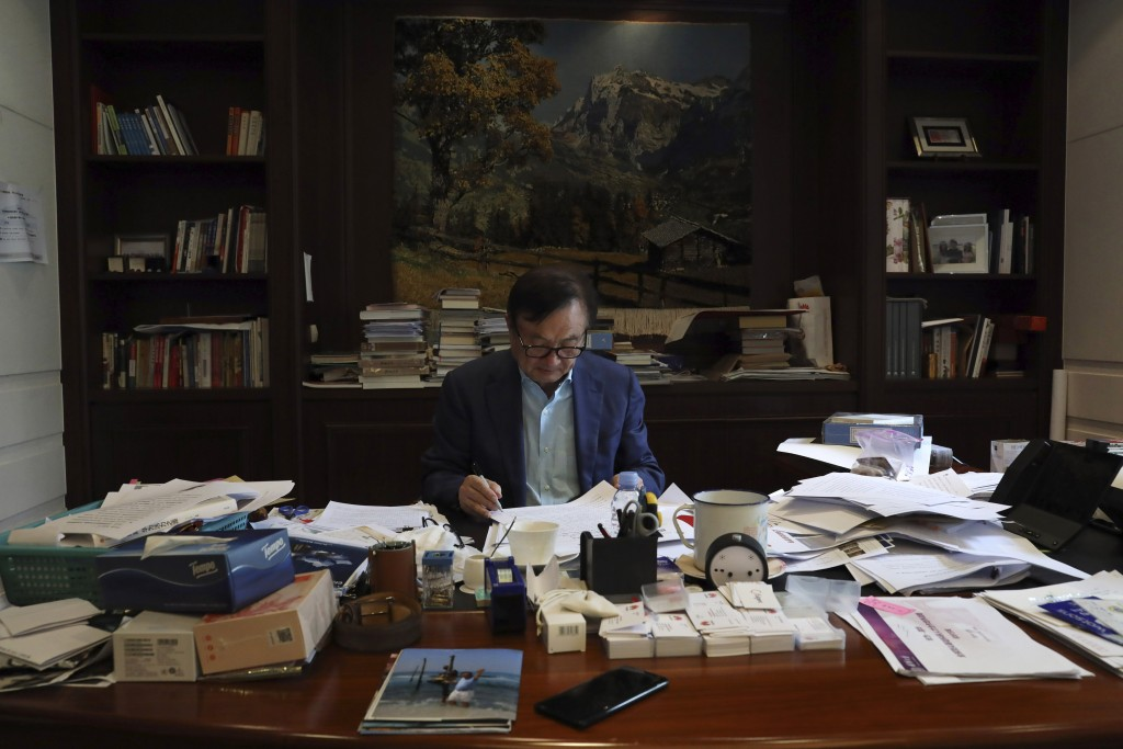 In this Aug. 20, 2019, photo, Huawei's founder Ren Zhengfei reads documents in his office at the Huawei campus in Shenzhen in Southern China's Guangdo...