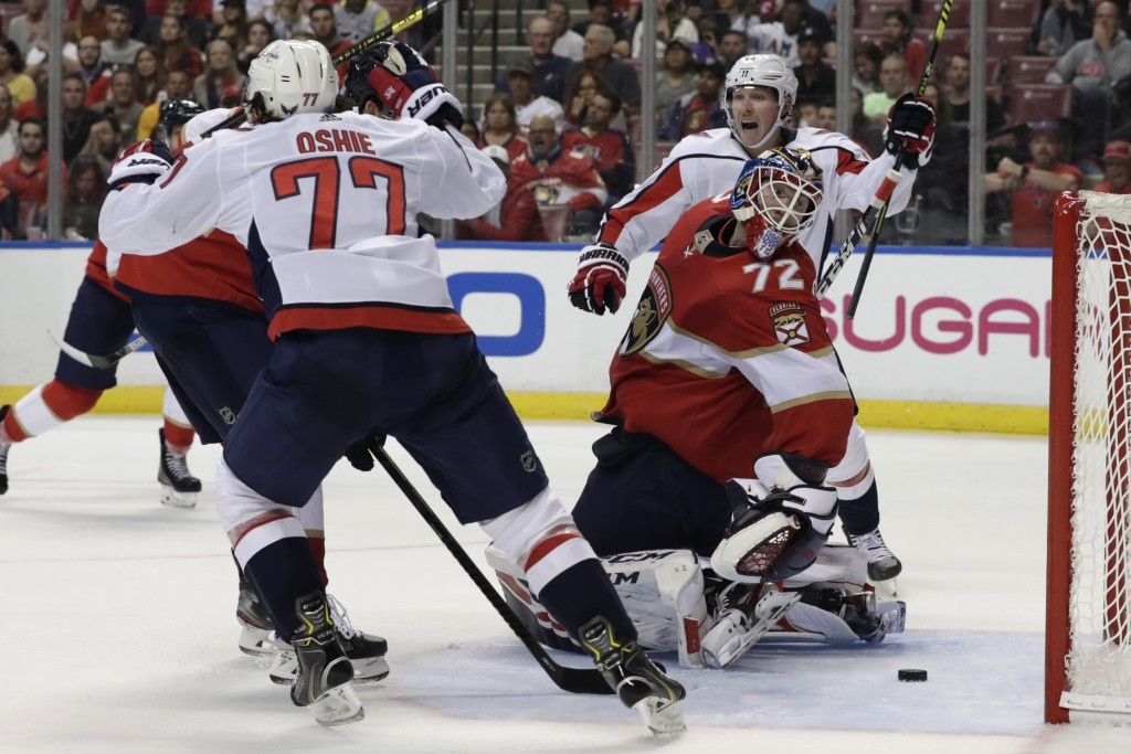 Florida Panthers goaltender Sergei Bobrovsky (72) looks back as Washington Capitals right wing T.J. Oshie (77) and center Nicklas Backstrom, right, re...