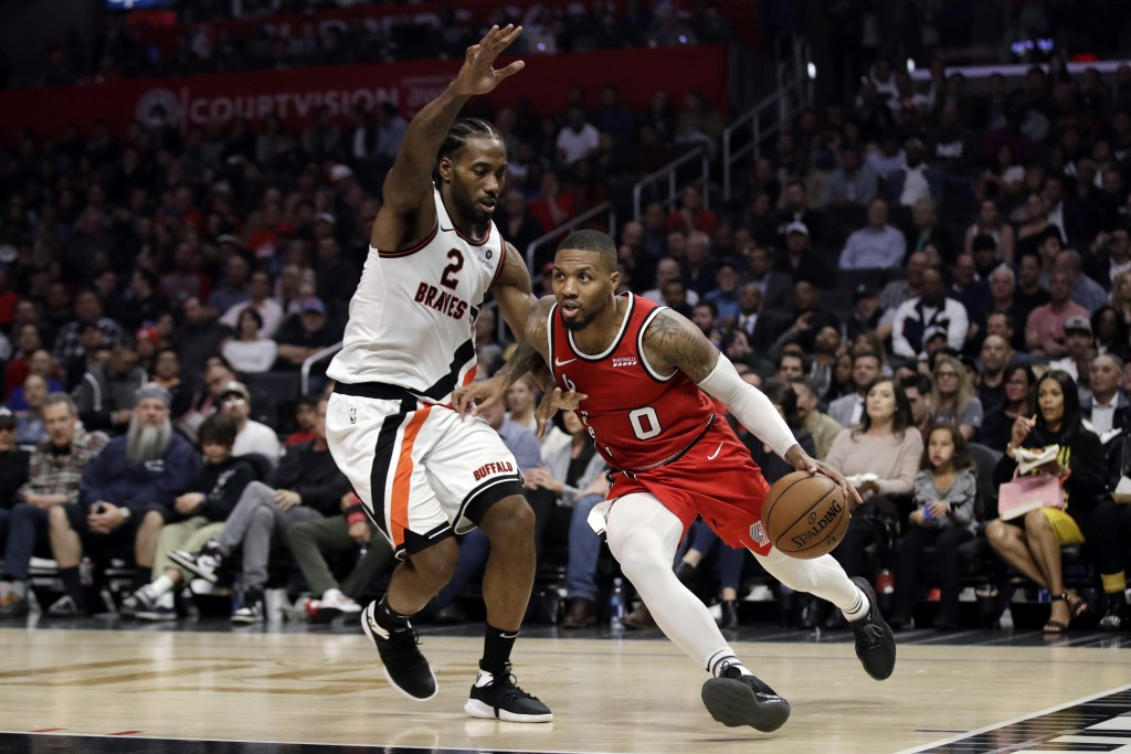 Portland Trail Blazers' Damian Lillard (0) dribbles next to Los Angeles Clippers' Kawhi Leonard (2) during the first half of an NBA basketball game Th...