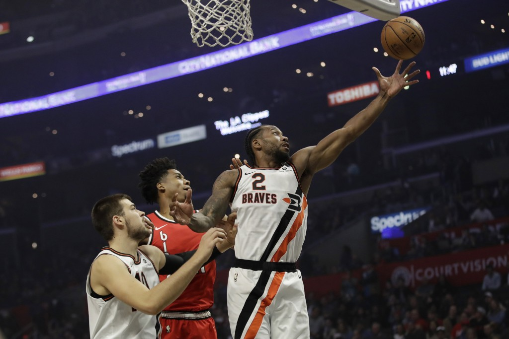 Los Angeles Clippers' Kawhi Leonard (2) grabs a rebound in front of Portland Trail Blazers' Hassan Whiteside, center, during the first half of an NBA ...