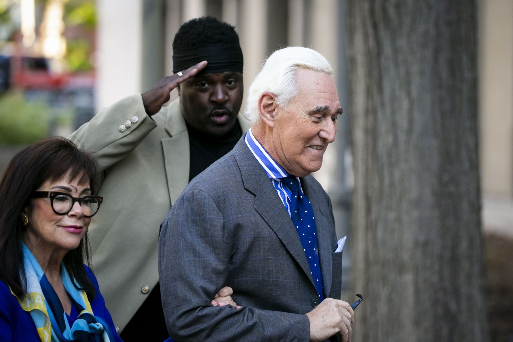 Roger Stone, and his wife Nydia, arrive as a man salutes him at Federal Court for his federal trial in Washington, Friday, Nov. 8, 2019. (AP Photo/Al ...