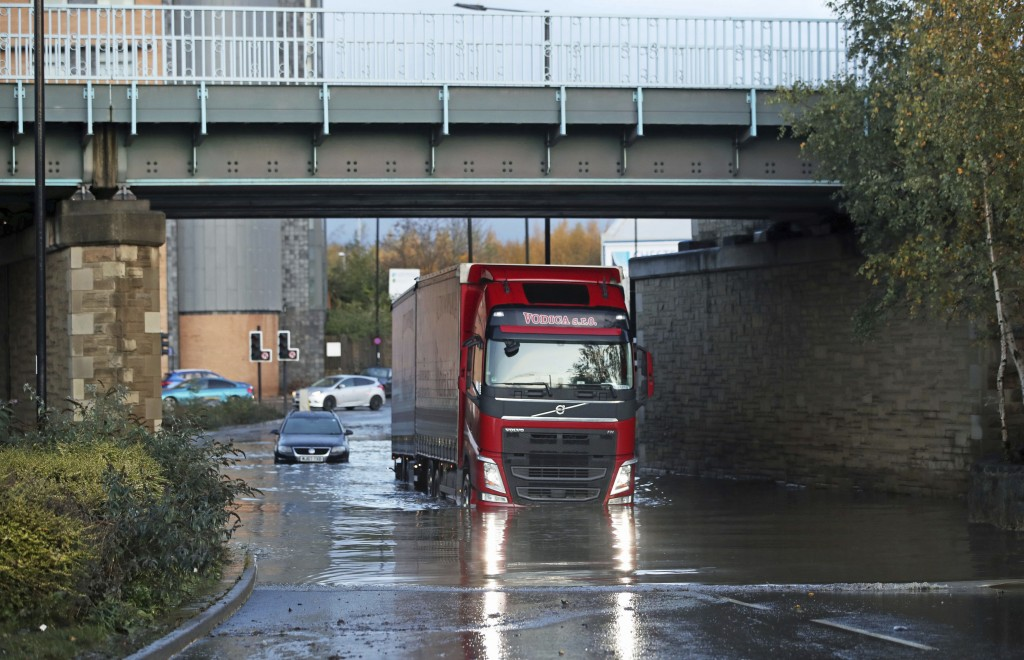 A lorry makes its way through floodwater near Meadowhall shopping centre in Sheffield, England, Friday Nov. 8, 2019, where some people were forced to ...