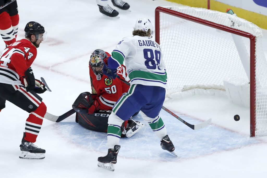 Vancouver Canucks' Adam Gaudette, right, is unable to get his stick on a bouncing puck as Chicago Blackhawks goaltender Corey Crawford (50) defends du...