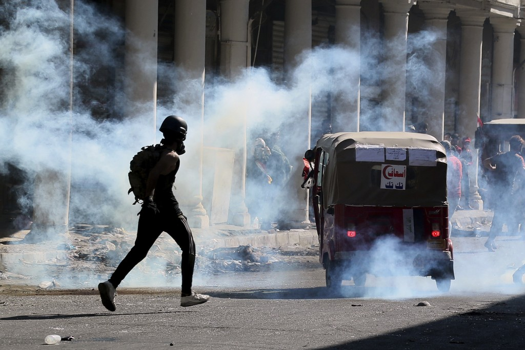 Iraqi riot police fire tear gas to disperse anti-government protesters during ongoing protests in Baghdad, Iraq, Friday, Nov. 8, 2019. Iraqi security ...