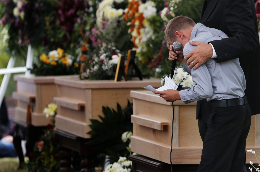 A boy pauses as he speaks next to the coffins of Dawna Ray Langford, 43, and her sons Trevor, 11, and Rogan, 2, who were killed by drug cartel gunmen,...