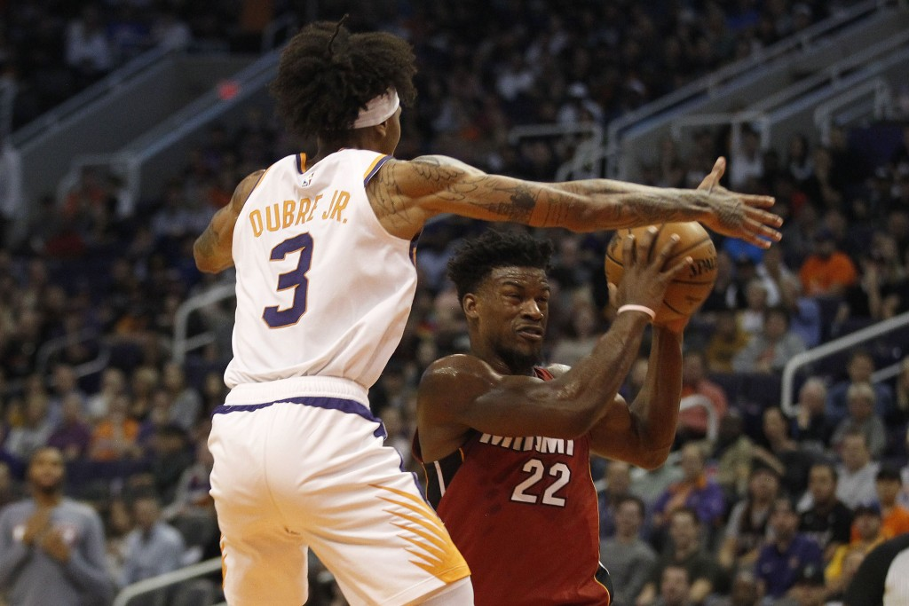 Phoenix Suns' Kelly Oubre Jr. (3) plays tough defense against Miami Heat's Jimmy Butler (22) during the first half of an NBA basketball game Thursday,...