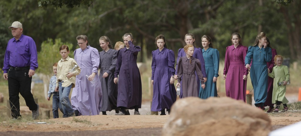 FILE - In this Sept. 26, 2015, file photo, people attend a memorial service in Hildale, Utah, for 12 women and children swept away in a deadly flash f...