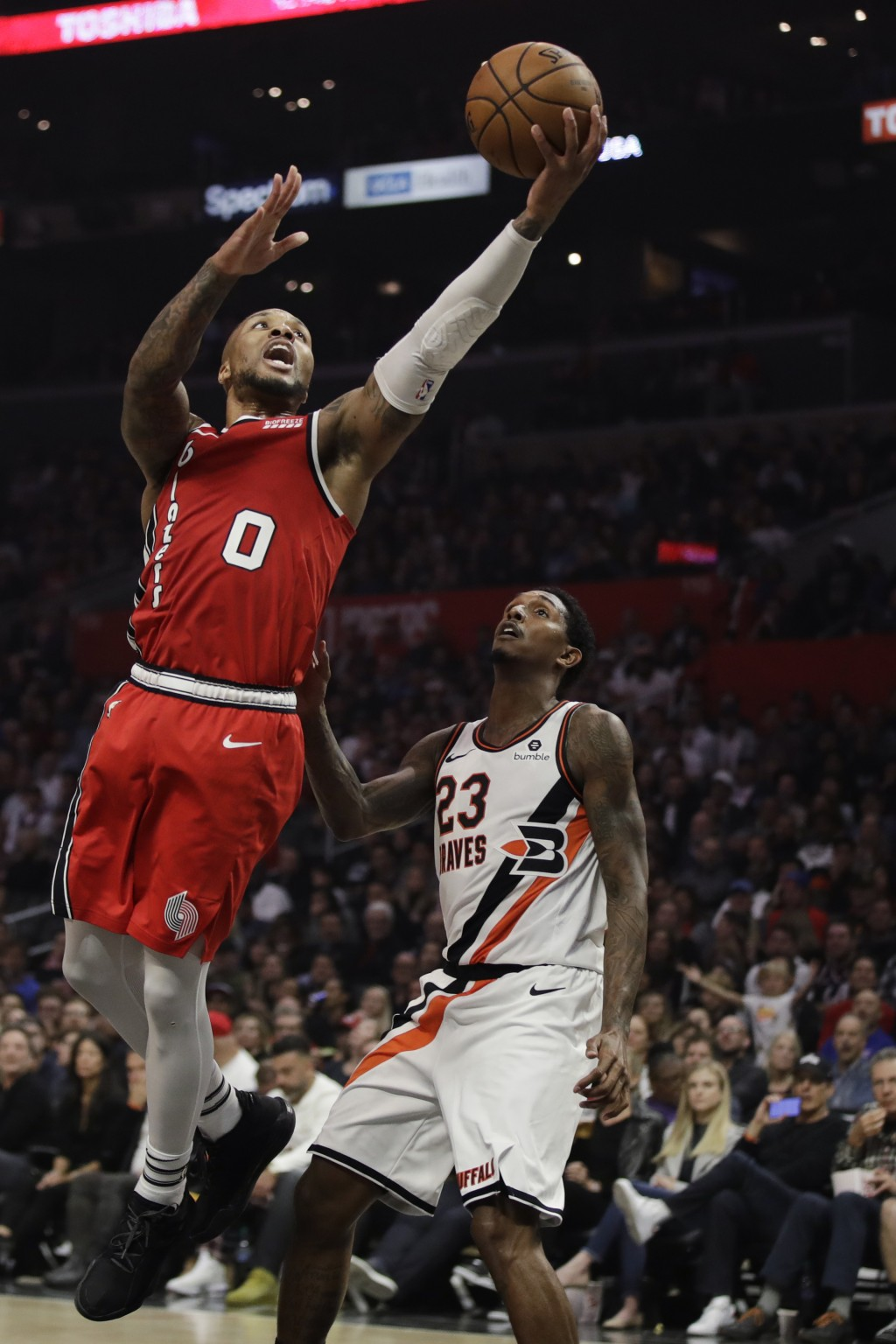 Portland Trail Blazers' Damian Lillard (0) scores past Los Angeles Clippers' Lou Williams (23) during the first half of an NBA basketball game Thursda...
