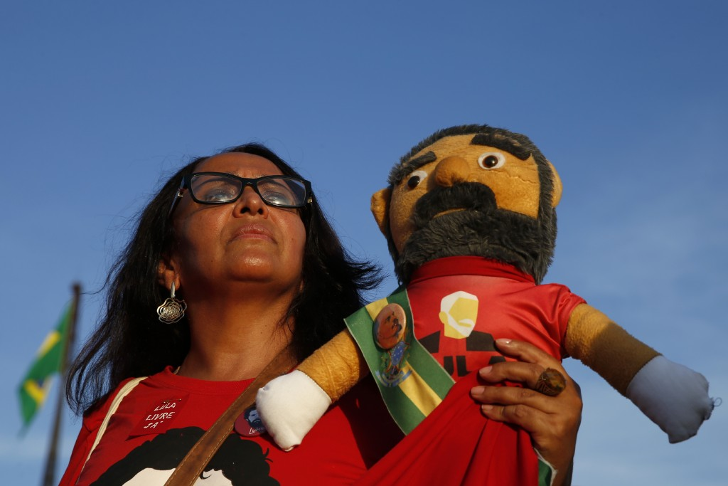 A supporter holds a doll depicting jailed former P...