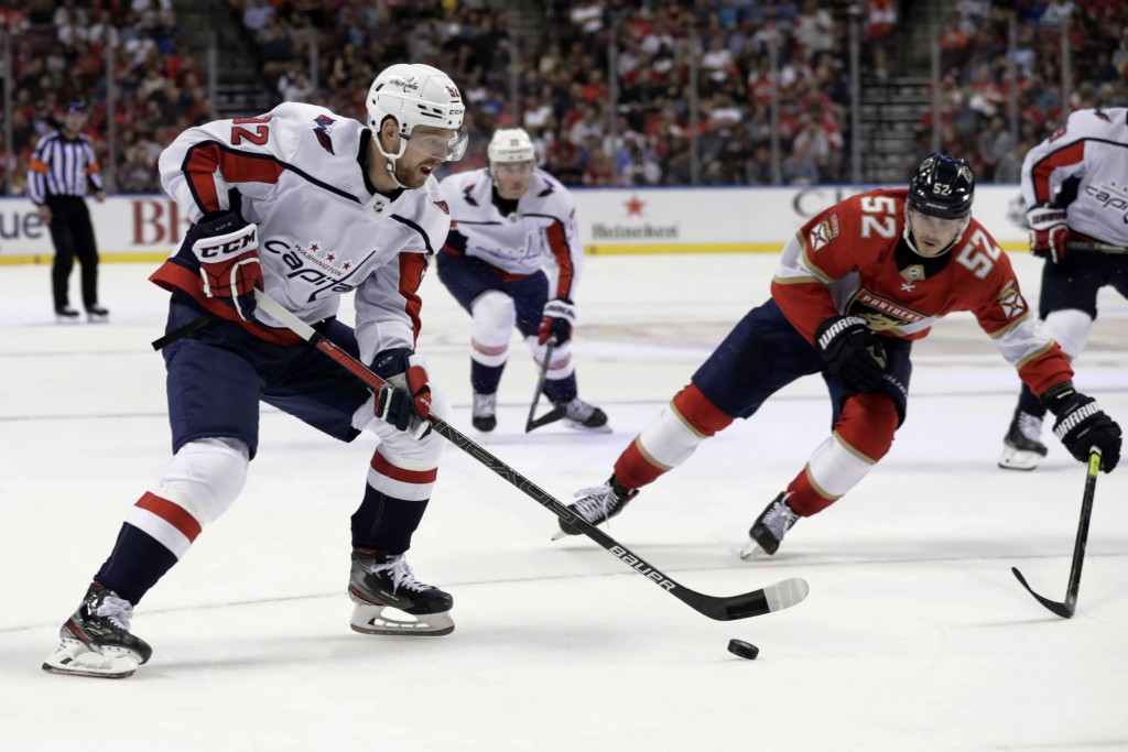 Washington Capitals center Evgeny Kuznetsov, left, skates with the puck as Florida Panthers defenseman MacKenzie Weegar (52) pursues during the second...