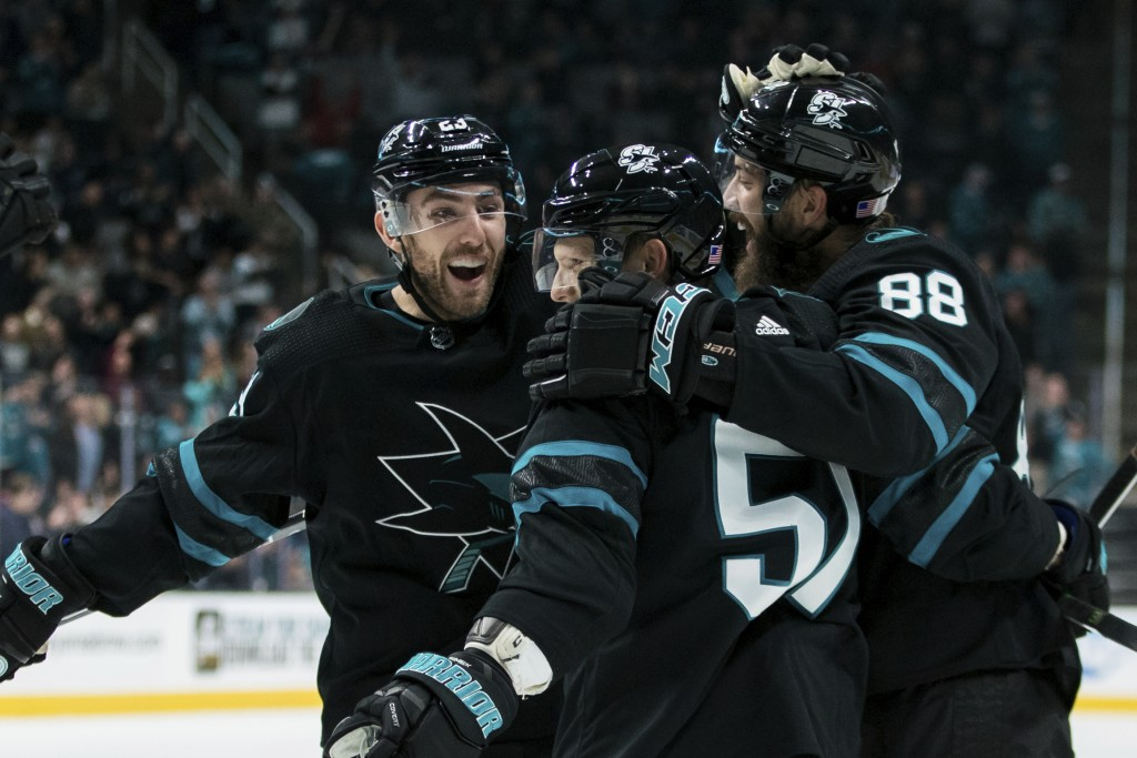 San Jose Sharks' Radim Simek, middle, is congratulated by Brent Burns (88) and right wing Barclay Goodrow, left, after scoring a goal against the Minn...
