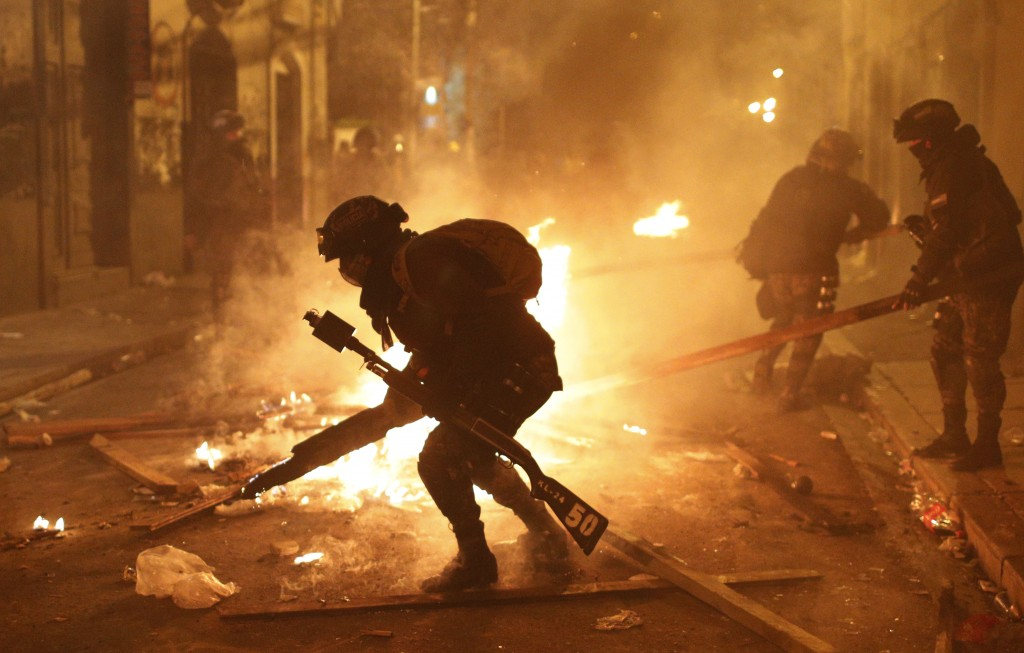 Police dismantle a burning barricade during a protest against the reelection of President Evo Morales, in La Paz, Bolivia, Thursday, Nov. 7, 2019. The...