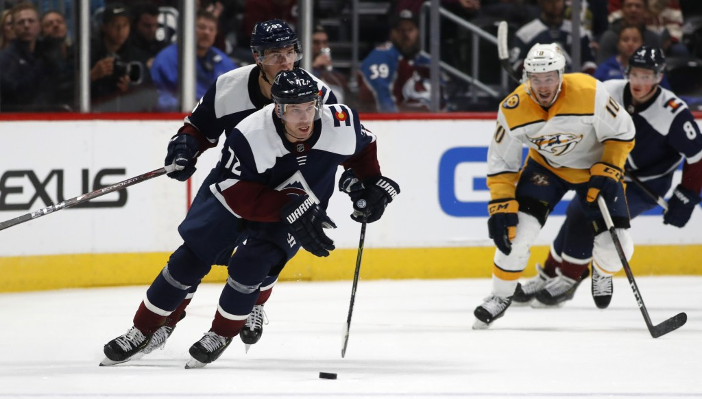 Colorado Avalanche right wing Joonas Donskoi, front, drives down the ice with the puck with left wing Andre Burakovsky, back left, and Nashville Preda...