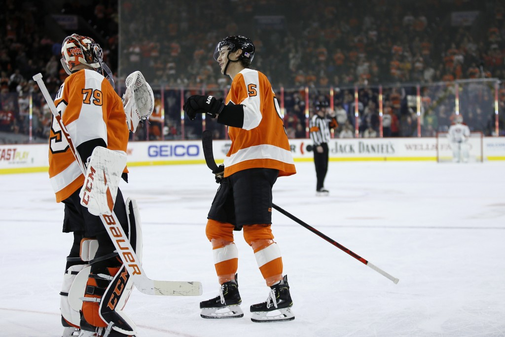 Philadelphia Flyers' Philippe Myers (5) and Carter Hart (79) celebrate after a goal by Myers during the first period of an NHL hockey game against the...