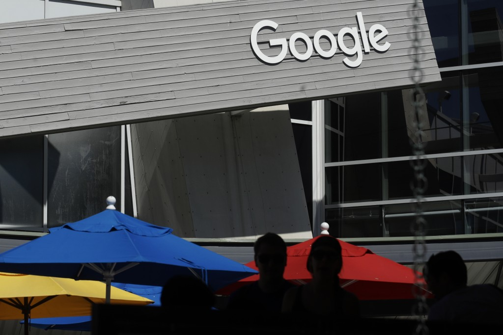 FILE - In this Sept. 24, 2019, file photo people walk by a Google sign on the campus in Mountain View, Calif. Alphabet's board of directors is investi...