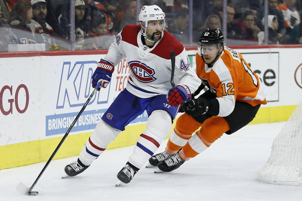 Montreal Canadiens' Nate Thompson (44) tries to keep Philadelphia Flyers' Michael Raffl (12) away from the puck during the second period of an NHL hoc...