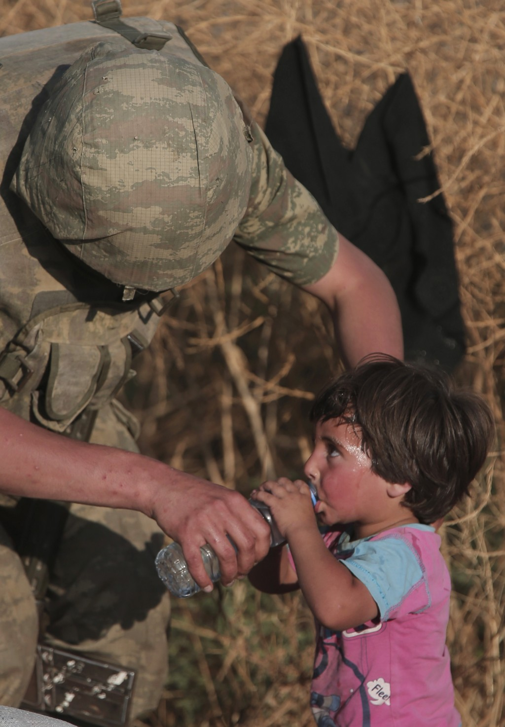 File - In this June 14, 2015, file photo a Turkish soldier offers water to a Syrian refugee child after crossing into Turkey from Syria, in Akcakale, ...