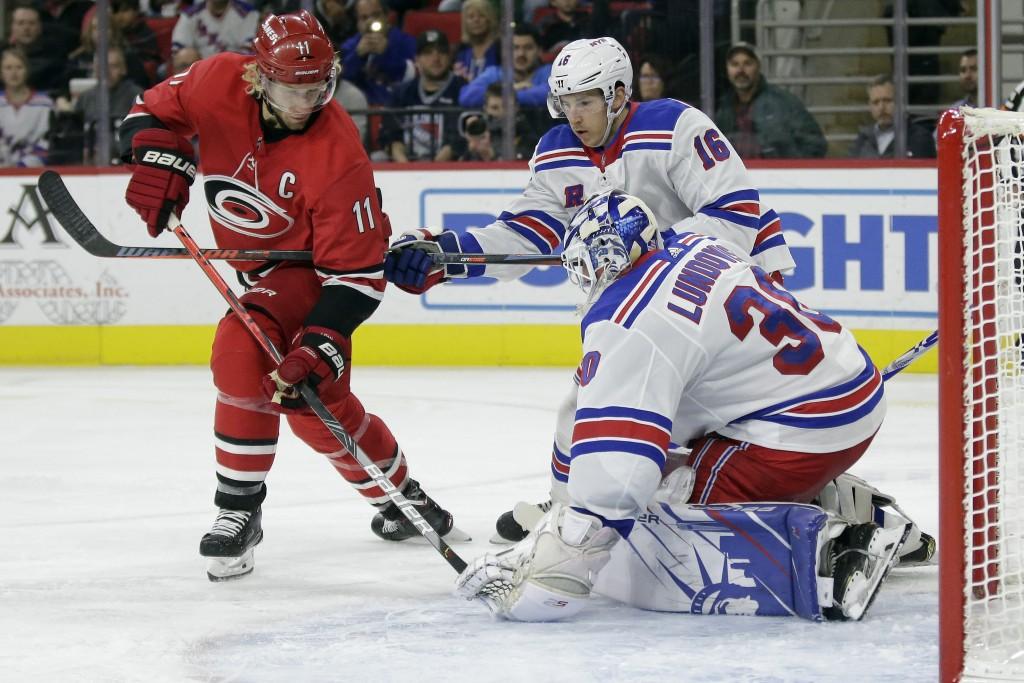 New York Rangers goaltender Henrik Lundqvist (30), of Sweden, blocks Carolina Hurricanes center Jordan Staal (11) while Rangers center Ryan Strome (16...