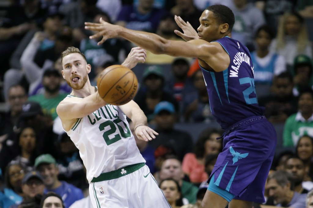 Boston Celtics' Gordon Hayward (20) gets a pass off against Charlotte Hornets' P.J. Washington (25) during the second half of an NBA basketball game i...