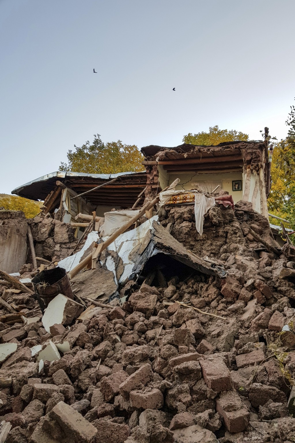 Debris lays amongst the ruins of collapsed buildin...