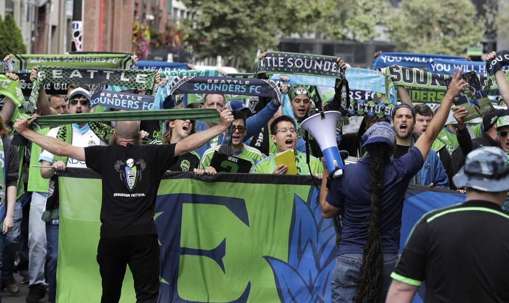 FILE - In this Sept. 1, 2018, file photo, members of the Emerald City Supporters hold up scarves during the traditional March to the Match before an M...