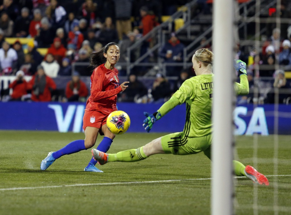 United States forward Christen Press, left, scores past Sweden goalkeeper Hedvig Lindahl during the first half of a women's international friendly soc...