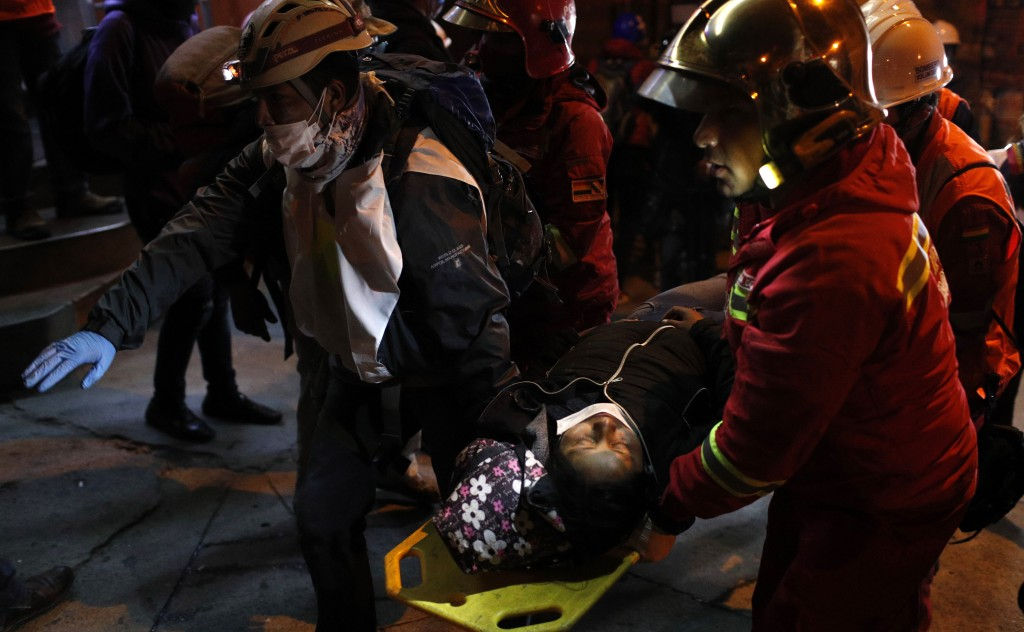 A woman injured in clashes with the police during a protest against President Evo Morales' reelection is carried to safety in La Paz Bolivia Thurs